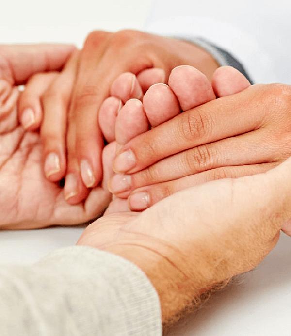 Nurse holding senior man hand at hospital