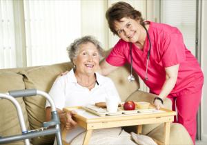 Friendly nurse brings a meal to an elderly