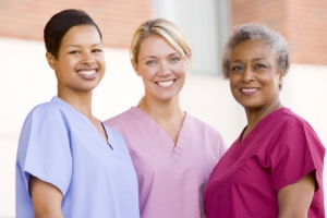 Nurses standing outside a hospital smiling